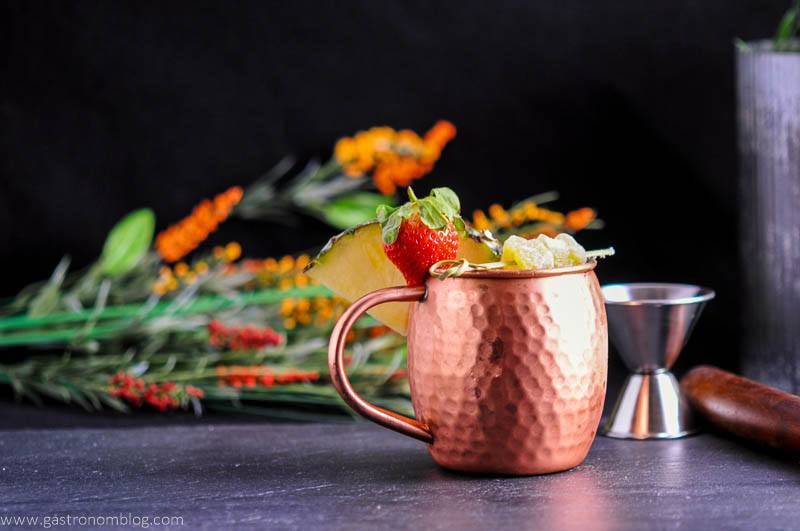 Spicy Pineapple Strawberry Moscow Mule in copper mug with ginger, pineapple wedge and strawberries. Jigger and flowers in background