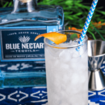 Clear cocktail in tall glass with blue and white straw on blue and white napkin