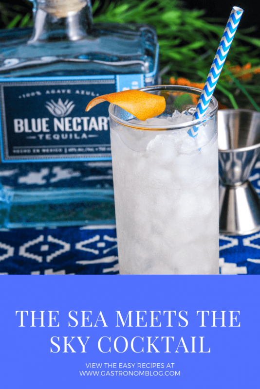 Where the Sea Meets the Sky Cocktail - in a tall glass with a grapefruit peel garnish and blue and white striped straw on a blue and white napkin, blue tequila bottle in background