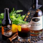 Brown cocktail in rocks glass with lemon peel, bottles behind