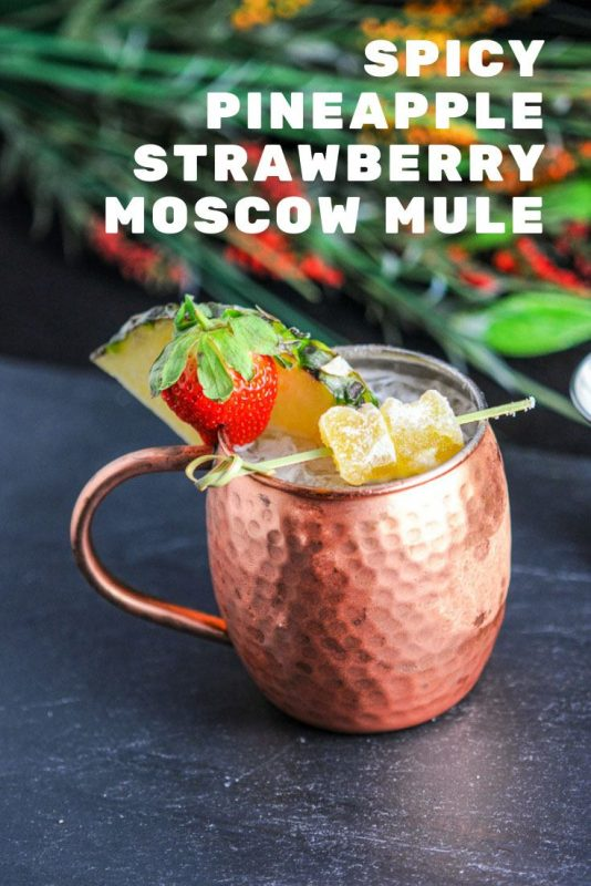 Spicy Pineapple Strawberry Moscow Mule in a copper mug with ginger, pineapple and strawberry