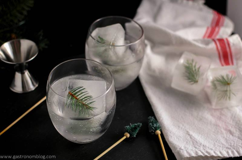 Mountain Pine Gin and Tonic with pine infused ice cubes. Pine topped cocktail stirrers and jigger with red and white napkin