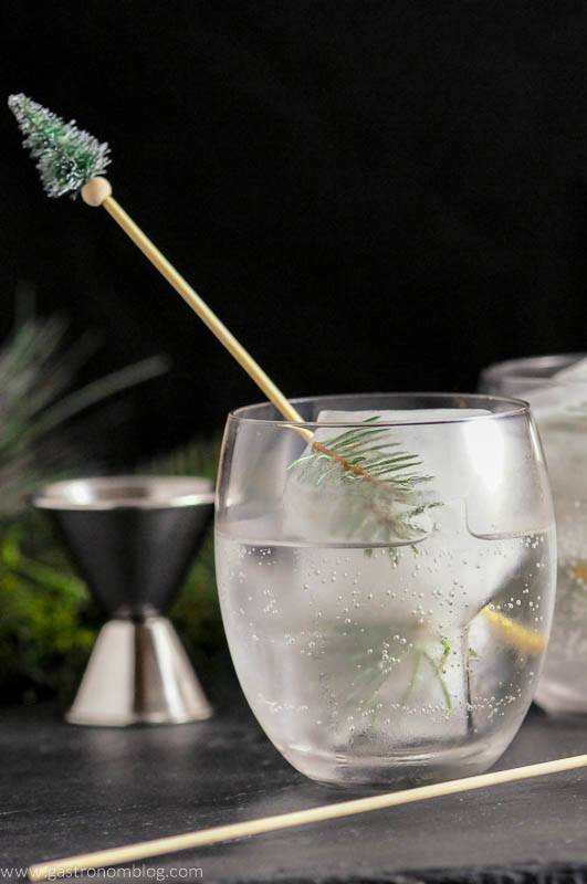 Mountain Pine Gin and Tonic with pine infused ice cubes and pine topped cocktail stirrer. Jigger in background