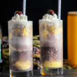 Puruple ice cream float in tall glasses, white and purple straws, cherries and whipped cream
