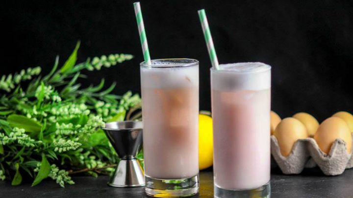 Raspberry Peach Ramos Gin Fizz, pink cocktails with white foam in highballs with green straws. Greenery, lemons and eggs in background