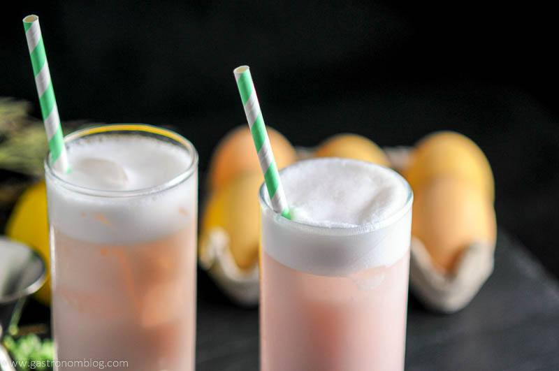 Raspberry Peach Ramos Gin Fizz in highball glasses with straws. Eggs and lemon in background