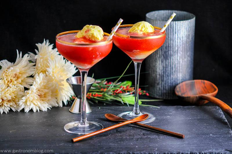 Strawberry Rhubarb Daiquiri Float in gold rimmed coupes, wooden spoons. Jigger, flowers and metal container in background
