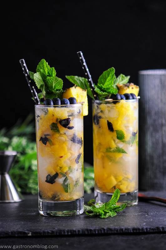 Blueberry Pineapple Mojitos in highball glasses with black and white polka dot straws, blueberries, mint and pineapple wedges.