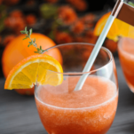 Orange cocktail in glass with orange slice and blue straw