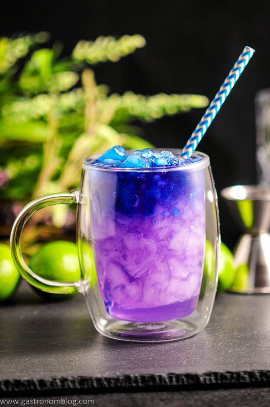 Galaxy Magic Mule in clear glass mug with blue straw. Limes and flowers in background. Color changing cocktail