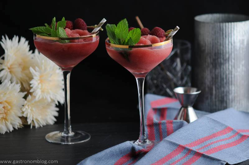 Watermelon Raspberry Frosé in coupes with straws, mint and raspberries. Flowers, blue napkin, jigger and metal canister in background