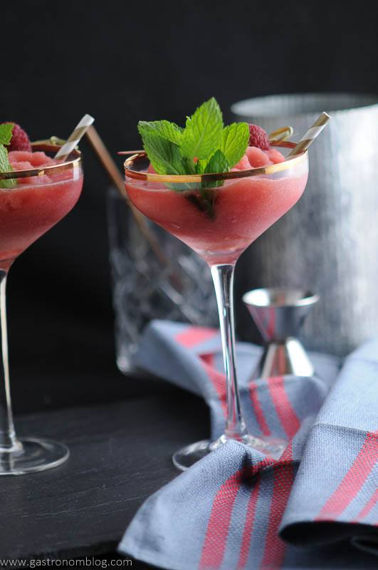 Watermelon Raspberry Frosé in cocktail coupes, mint and straws. Blue napkin, jigger and metal canister in background.