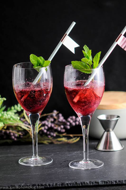 Blueberry Mint Sorbet Rose Float in wine glasses with mint and straws. Jigger and gray container in background with flowers.