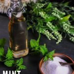 Bottle of mint simple syrup with bowl of sugar and greens behind