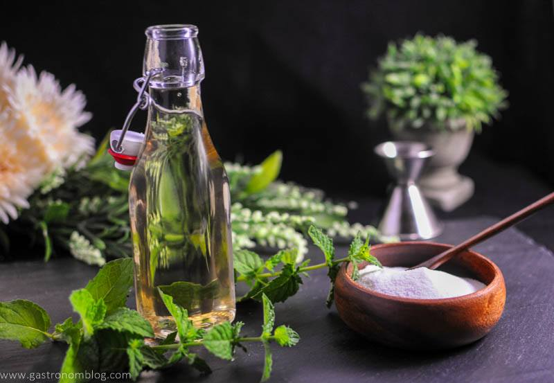 Mint Simple Syrup in bottle with wooden bowl filled with sugar. Mint leaves, flowers and jigger in background