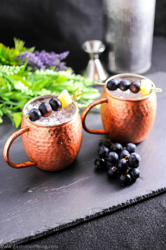 Concord Grape Moscow Mule in copper mugs with grapes and ginger on cocktail pics. Bunch grapes, flowers, jigger and metal canister in background