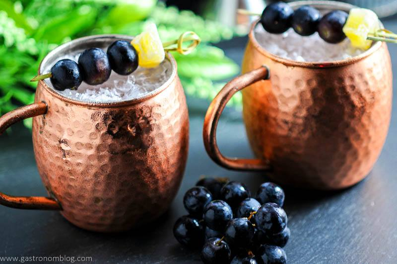 Concord Grape Moscow Mule in mugs with grapes and ginger.