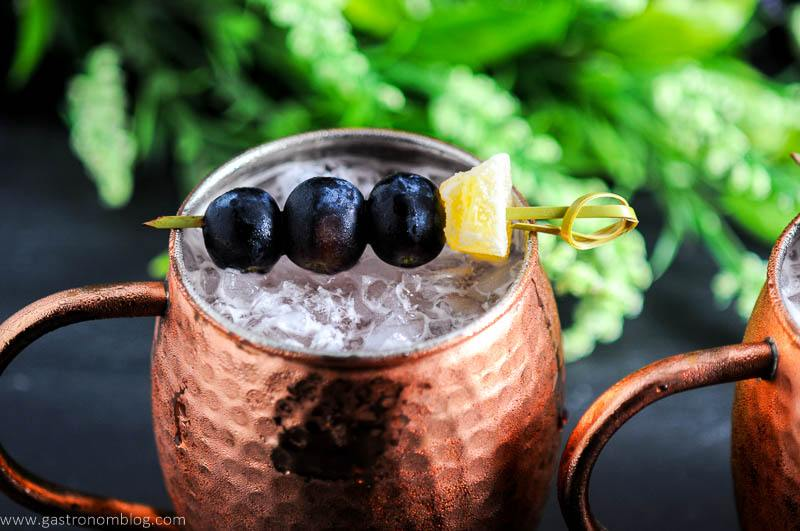 Concord Grape Moscow Mule in copper mug. Grapes and ginger on cocktail pick. Flowers in background