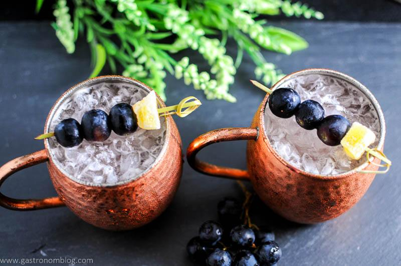 Concord Grape Moscow Mule in copper mugs. Grapes and ginger on cocktail picks. Flowers in background