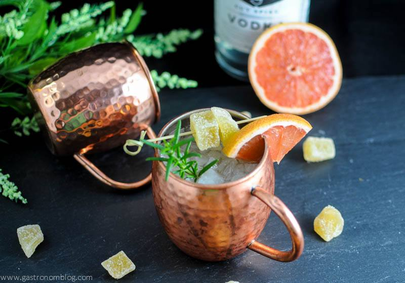 Rosemary Grapefruit Moscow Mule in copper mugs with grapefruit slices, ginger and rosemary. Vodka bottle and flowers in background