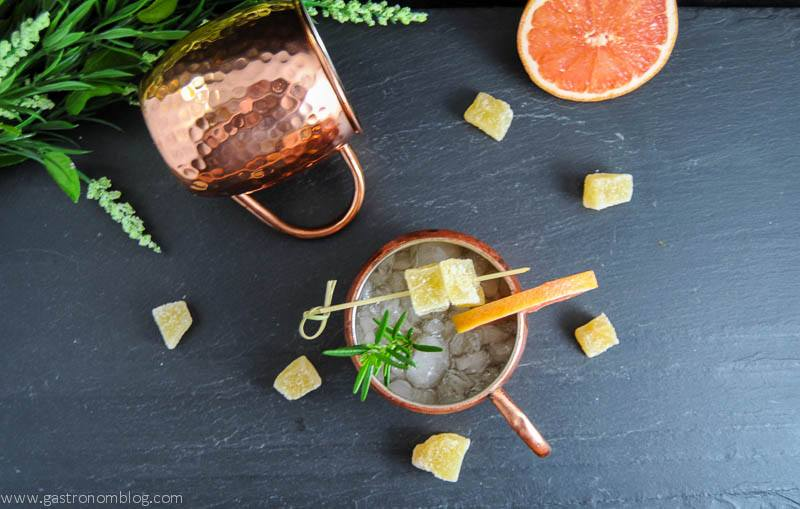 Rosemary Grapefruit Moscow Mule in copper mugs with grapefruit slices, ginger and rosemary sprigs. Flowers in background