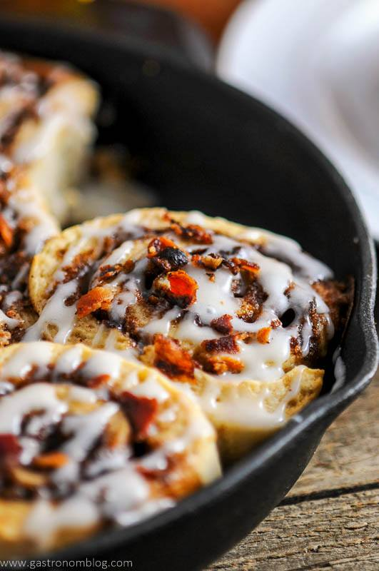 Bourbon bacon cinnamon rolls in a cast iron pan.