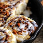 Bourbon Bacon Cinnamon Rolls topped with bacon and in skillet