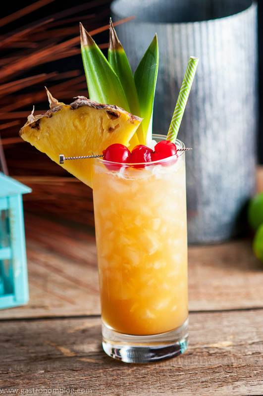 Fresh pineapple and candied cherries garnish the Fall in Paradise cocktail, a tiki cocktail full or great flavors!