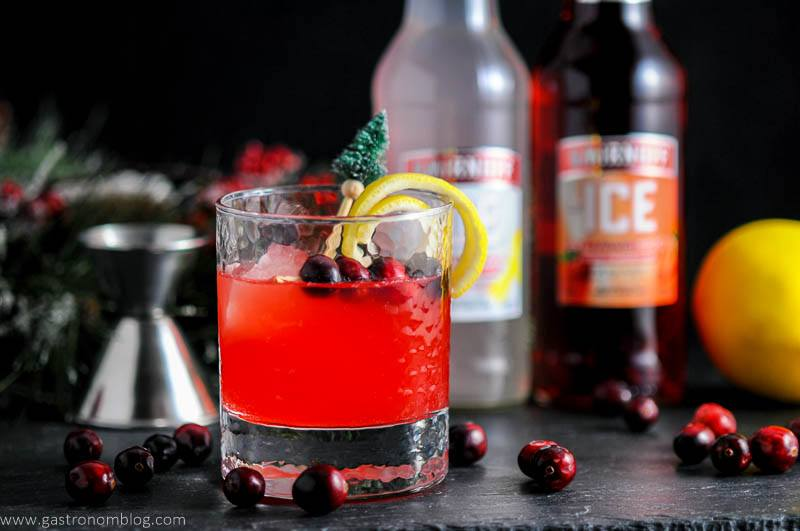 Holiday Berry Sparkler Cocktail in rocks glass with cranberries, lemon peel and pine tree topped stirrer. Jigger, cranberries, lemon and Smirnoff Ice bottles in background