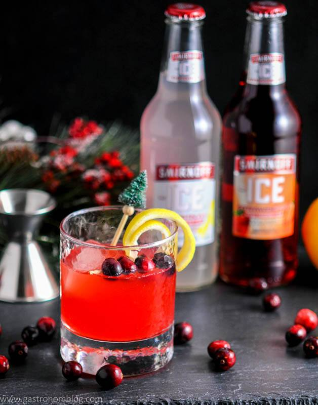 The Holiday Berry Sparkler Cocktail features Smirnoff Ice Original and Smirnoff Ice Strawberry, apple cider, cranberry simple syrup and and triple sec to make a delightfully delicious holiday party drink!