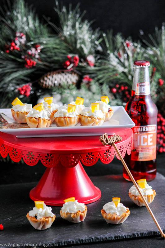 Mini Berry Bites on red cake stand and slate. With fir branch and strawberry Smirnoff Ice bottle in background.