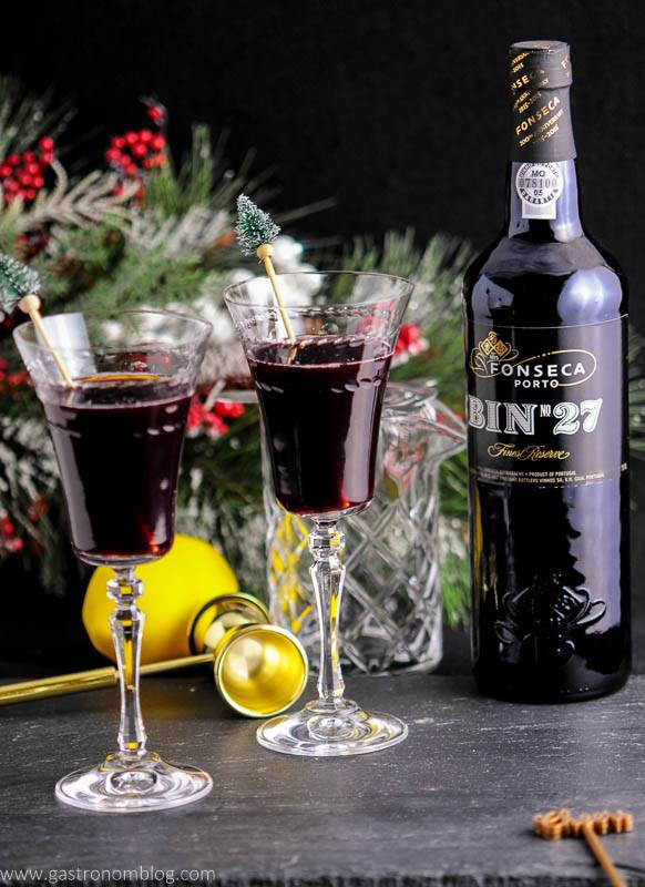 Two Recap Cocktails, made with Bin 27 Port Wine, amaro, mint and lemon sits in front of holiday decor, a gold double jigger and a bottle of port wine.