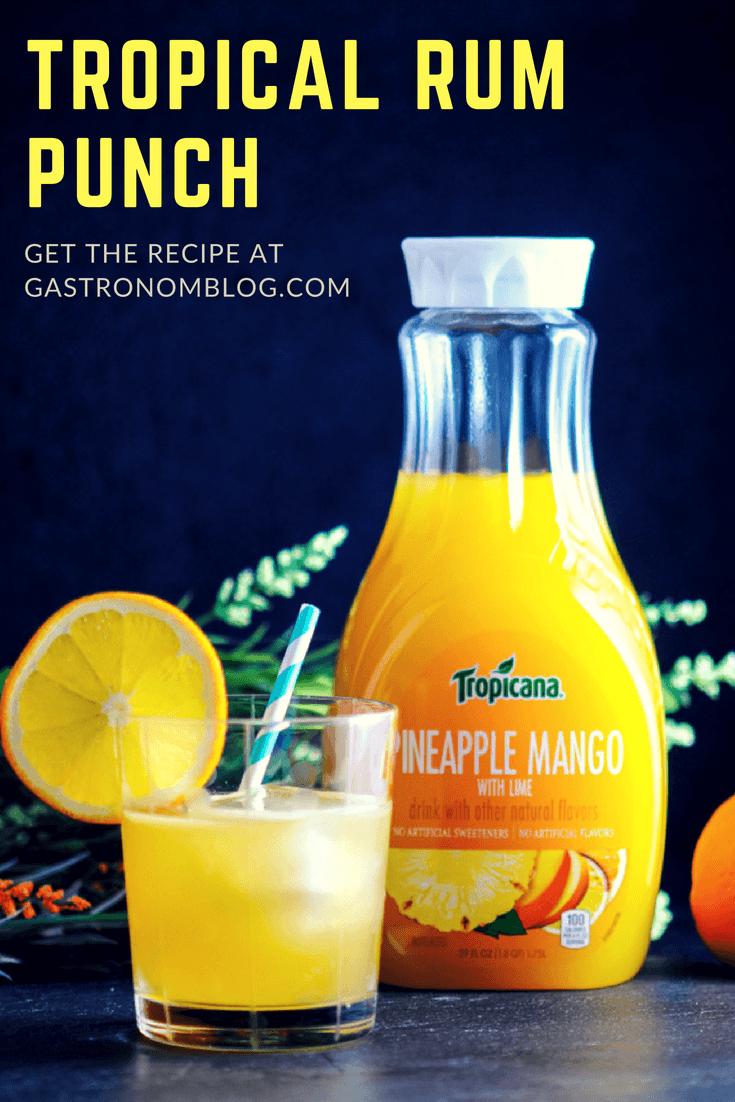 Tropical Rum Punch with Tropicana - champagne, sparkling wine, pineapple mango juice, lime juice, triple sec, rum, bitters from Gastronomblog. This rum punch cocktail is an easy dark rum punch with the flavors of the Caribbean! #sponsored #cocktail #rum #pineapple #gastronomblog