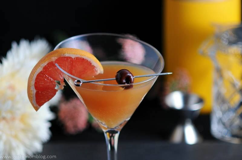 Apple Cider Sidecar in a martini glass with brandied cherry and a grapefruit ganish.