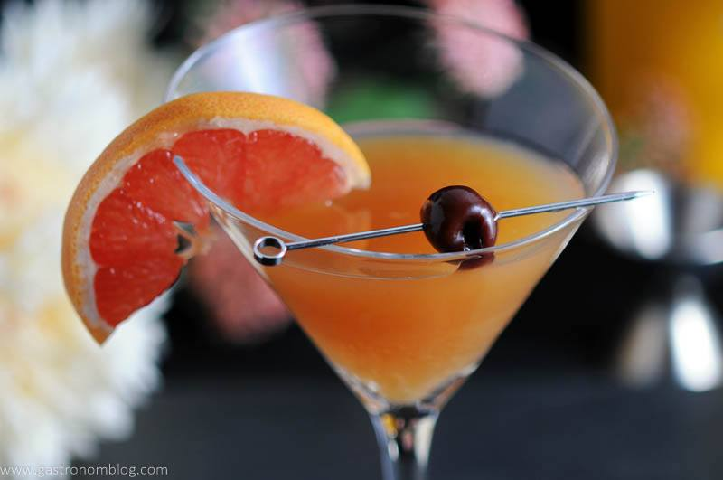 The Apple Cider Sidecar in a martini glass with a cherry on a cocktail pick and a slice of grapefruit. A jigger and flowers in the background.