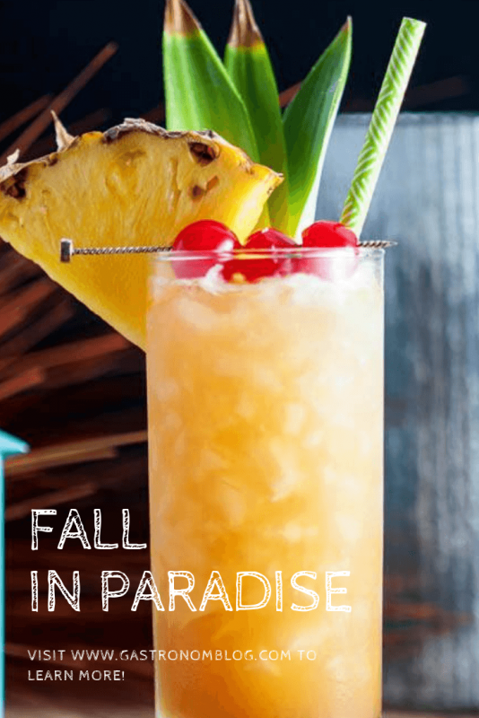 Fall in Paradise cocktail in a tall glass with cherries, pineapple and pineapple leaves
