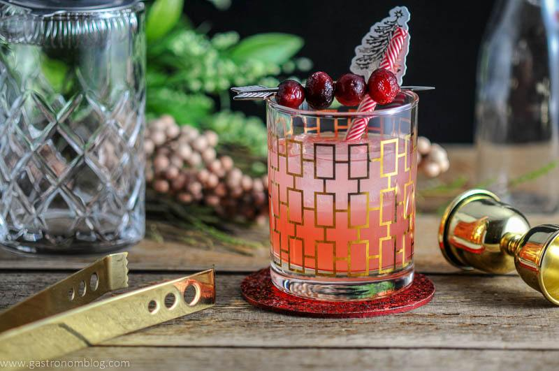 The Red Hound Cocktail made with cranberry, fresh grapefruit, elderflower liqueur and vodka, in a rocks glass and garnished with cranberries and straws, on a wooden table.