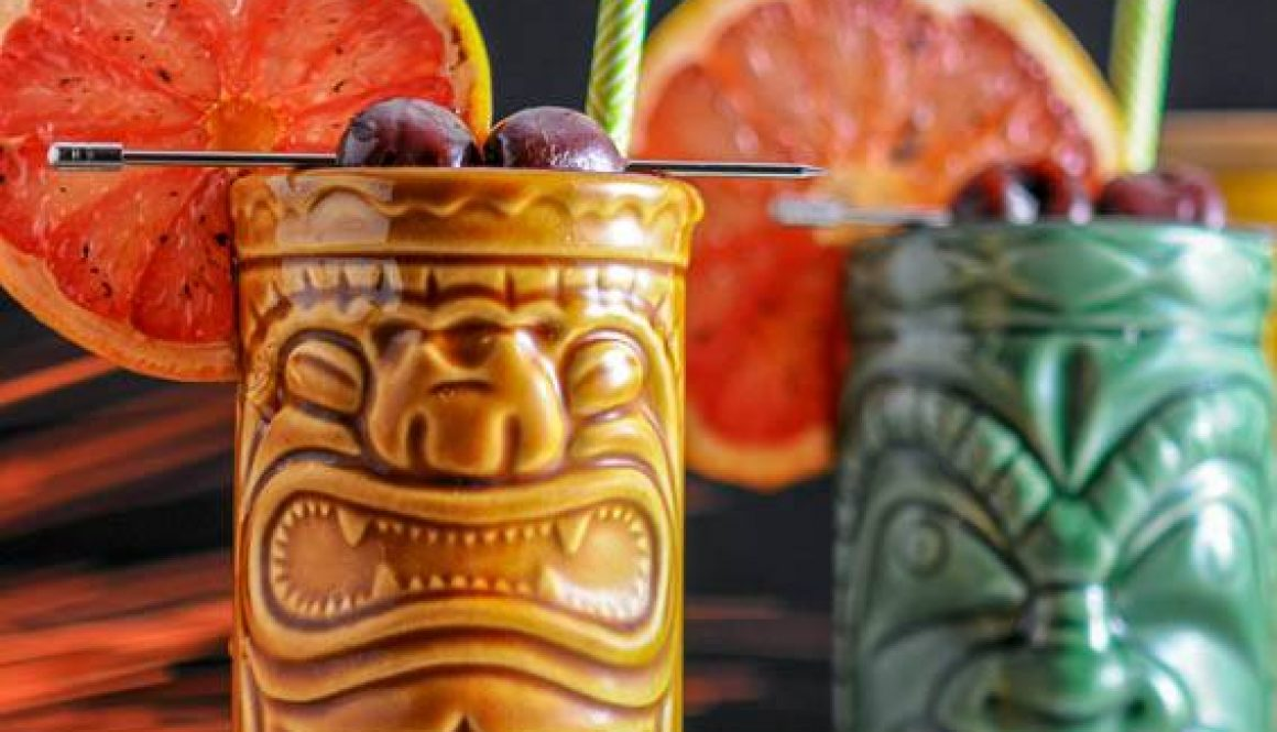 Close up of a pair of tiki glasses filled with The Rambler's Ruby, a tiki cocktail garnished with brandied cherries and a bruleed grapefruit.