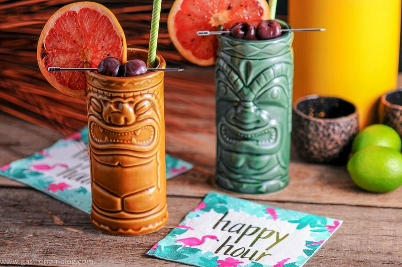 A pair of tiki glasses full of The Rambler's Ruby, a tiki cocktail made with Gin and Mezcal.