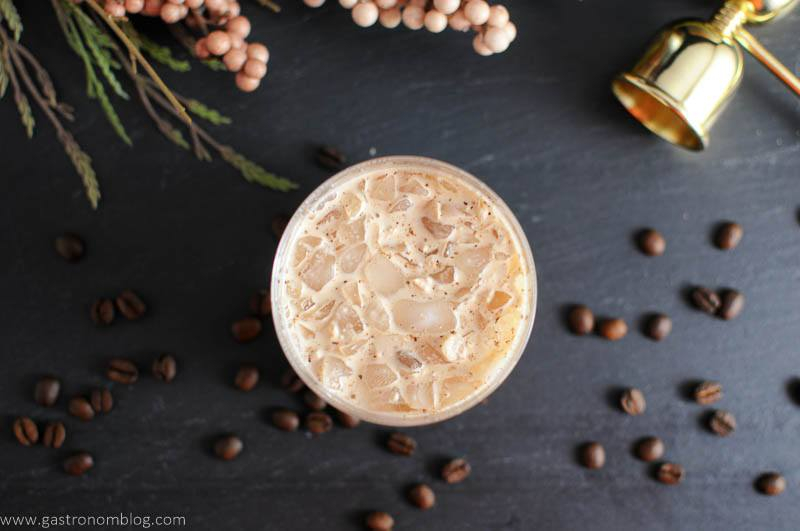 A Chai Toasted Cream White Russian sits in a rocks glass surrounded by coffee bean garnishes!