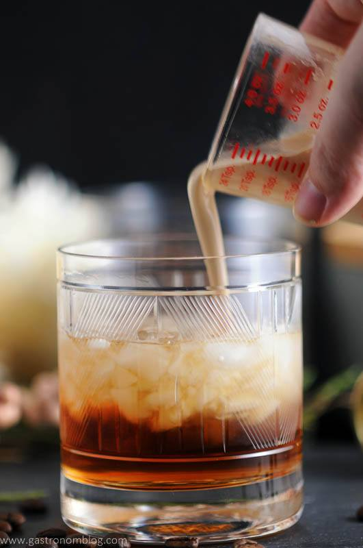 Toasted cream is poured into a rocks glass containing a mixture of Kahlua, vodka and chai tea simple syrup, making a Chai Toasted Cream White Russian Cocktail.