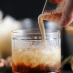 Cream being poured into a white russian cocktail