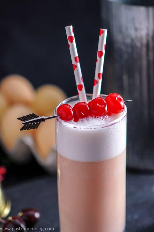 an arrow cocktail pick pieces maraschino cherries that garnish a Cherry Toasted Cream Ramos Gin Fizz