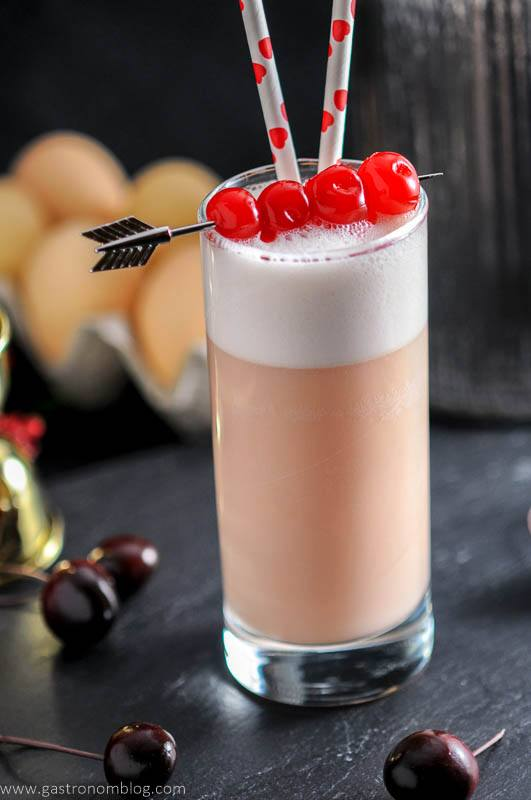 Maraschino cherries top a highball glass filled with a Cherry Toasted Cream Ramos Gin Fizz.