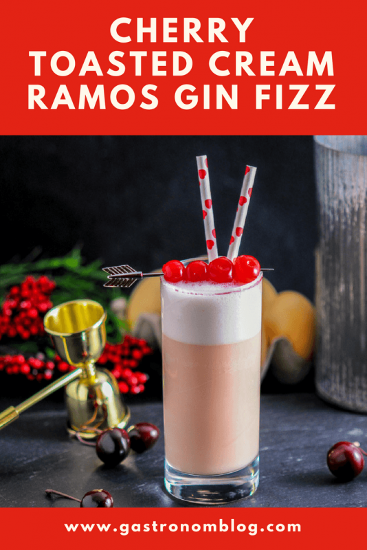 Cherry Toasted Cream Ramos Gin Fizz, pink cocktail with white foam in highball. maraschino cherries, hearts straws. Gold jigger, flowers, eggs and cherries around glass