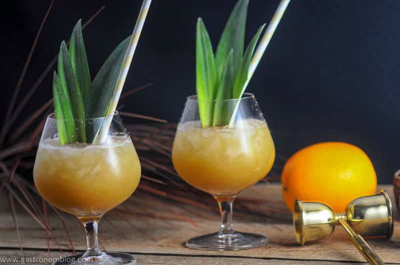 Coconut Rum Painkillers in brandy glasses with pineapple fronds and straws. Orange, ounce measure in background.