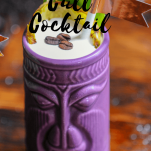 Purple tiki mug with foam, coffee beans and pineapple fronds
