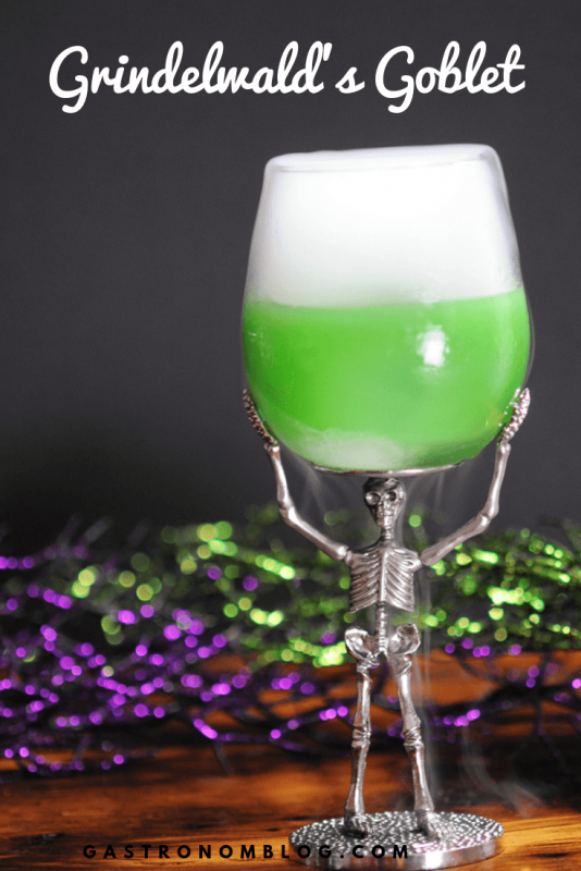 A green Halloween cocktail in a wine glass supported by a silver skeleton. Dry ice effect.