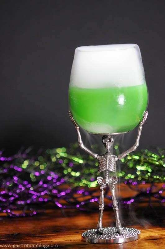 The Grindelwald Goblet - A green Halloween cocktail in a skeleton wine glass with dry ice smoke coming from it.
