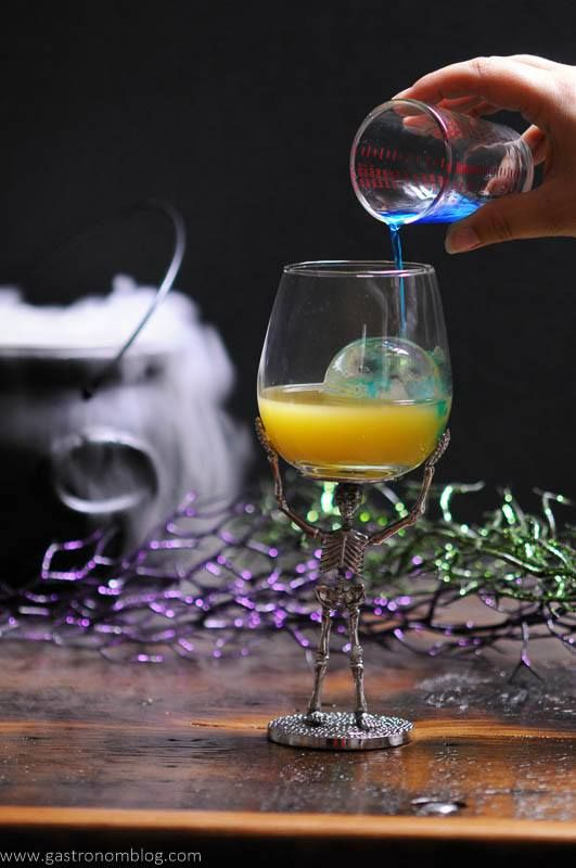 A wine glass supported by a metal skeleton holds a halloween cocktail while blue curacao is poured into it.